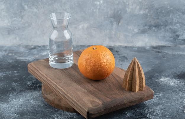 Одиночный апельсин и стекло на деревянной доске.