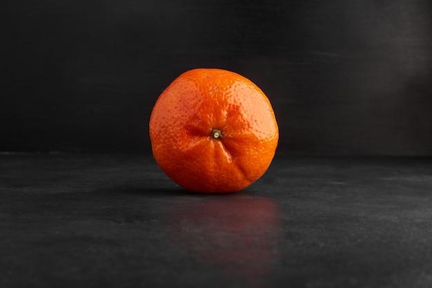 Одиночный апельсин, изолированные на черном фоне.