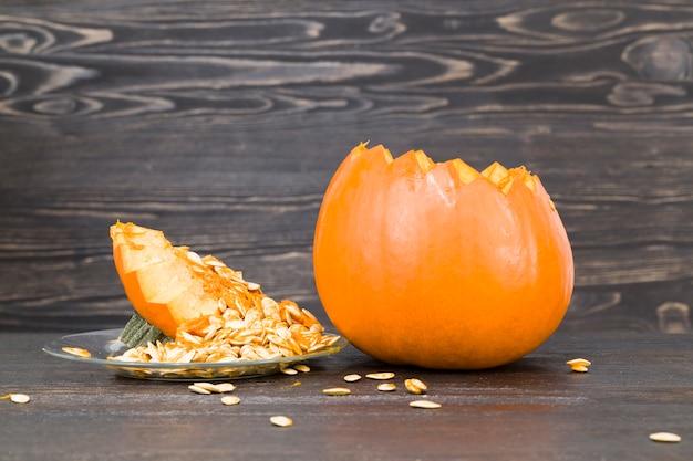 Одиночная оранжевая тыква, лежащая на черном деревянном столе, вырезанная для лампы jack на хэллоуин, крупным планом на кухне