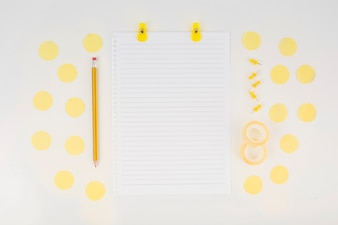 Single paper and pencil surrounded with elements on white background