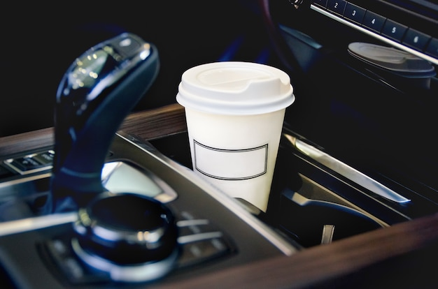 A single paper coffee cup inside the car cup holder.