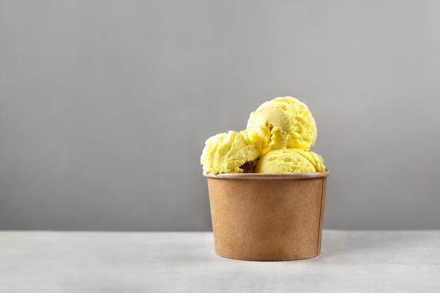 コピースペースのある灰色の壁に明るい黄色のアイスクリームボールまたはスクープが付いた単一の紙コップ。カラートレンド2021。ゼロウェイストとプラスチックフリーのコンセプト