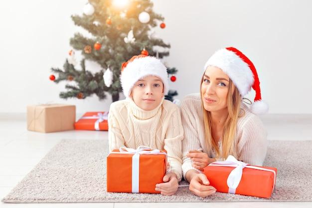 ひとり親と休日の概念-クリスマスイブに自宅でクリスマスを祝う母親の肖像画。