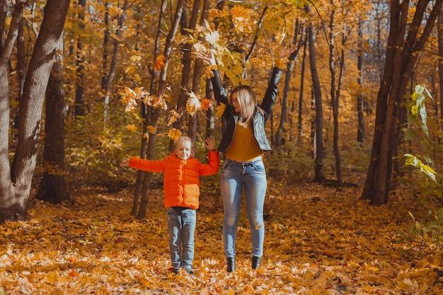 公園で紅葉で遊ぶひとり親家庭。幸せな母と息子は秋の公園に紅葉を投げます。