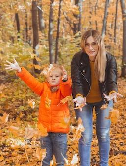 公園で紅葉で遊ぶひとり親家庭幸せなママと息子が紅葉を投げる