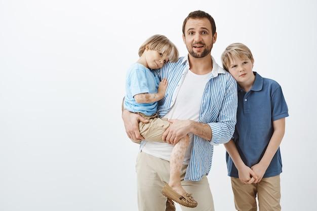 Genitore single che si occupa dei figli. papà che tiene un bambino carino con vitiligine mentre fissava nervosamente, essendo lasciato solo con due ragazzi, all'oscuro di come prendersi cura dei bambini