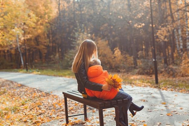 공원에서 가을에 한 부모 엄마와 아이 소년은 벤치 가을 시즌과 가족 개념에 앉아