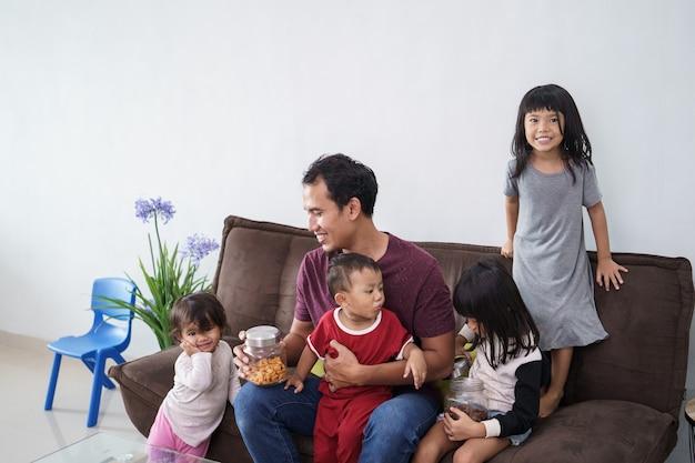 Одинокий родитель папы с 4 детьми сидит на диване дома