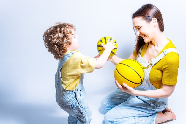 Single parent young adult mother playing with her son with a basketball and football. concept play with children. single mother. school sports