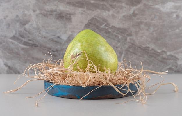 Una sola pera su un mucchio di paglia in un piccolo piatto blu su marmo
