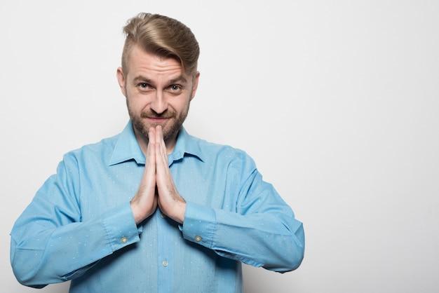 Одинокий задумчивый бородатый мужчина в синей рубашке со спокойным выражением лица
