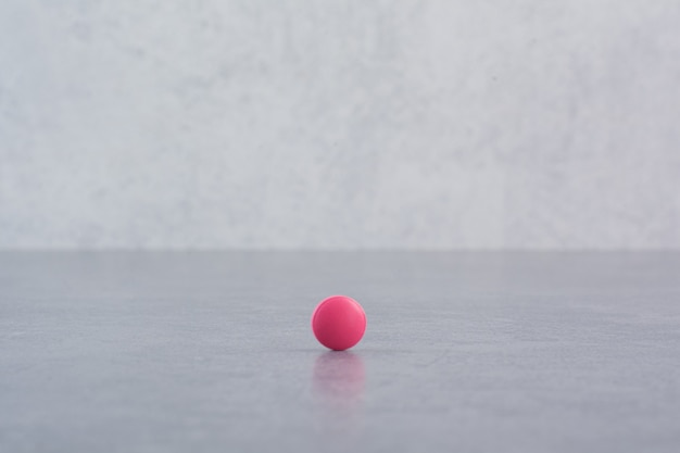 Single pink pill on marble table.