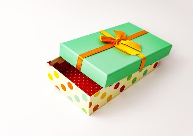 단일 폴카 도트 선물 종이 골판지 상자 녹색 덮개와 흰색 활. 휴일 선물 개념. 보기를 닫습니다. 선택적 소프트 포커스. 텍스트 복사 공간.