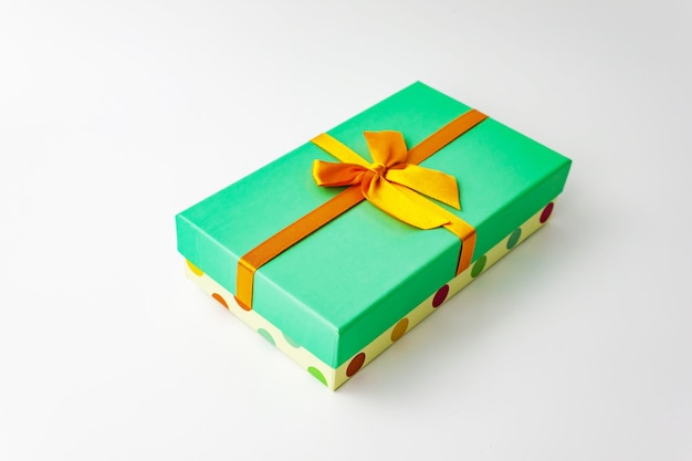 Single polka dot gift paper cardboard box with green cover and bow on white . holiday present concept. close up view. selective soft focus. text copy space.