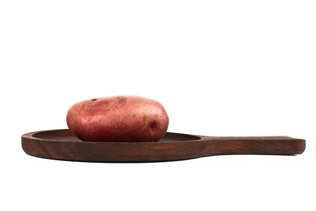 Один картофель на деревянном блюде.