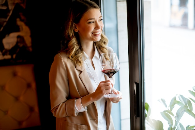 Single pretty young woman with glass of red wine standing near window and looking aside