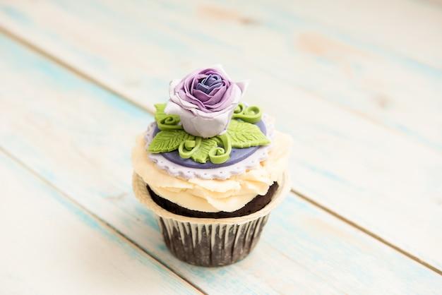 木製の花と単一の紫のカップケーキ