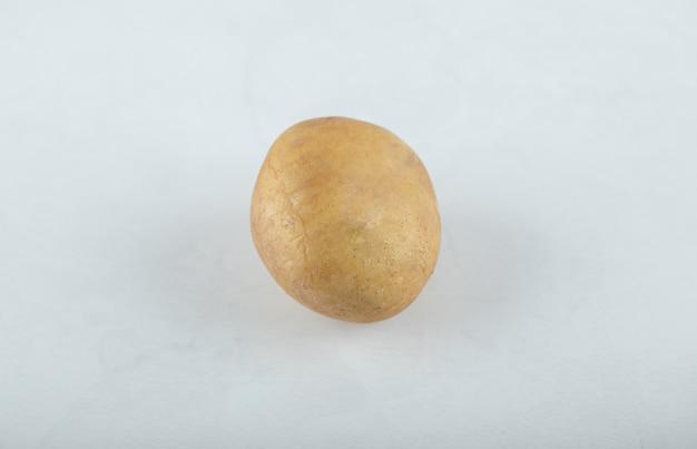 Una singola patata matura cruda su fondo bianco.