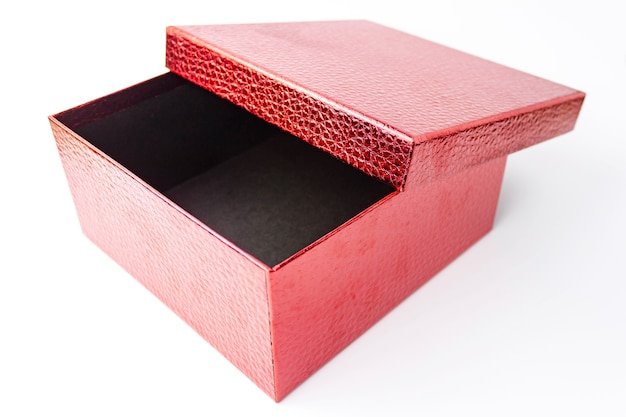 Single red color open gift paper cardboard leather embossed box on white . holiday present concept. close up view. selective soft focus. text copy space.