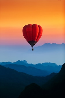 Single red hot air balloon flying over blue mountains