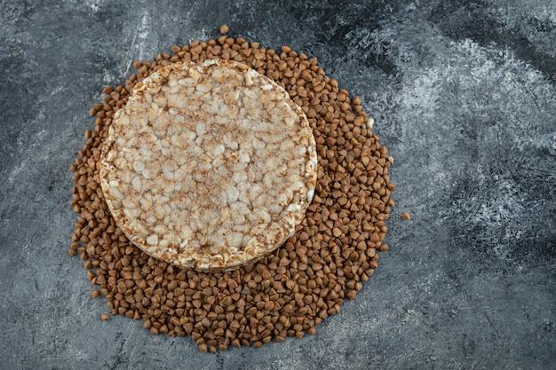 Singola torta di riso e grano saraceno crudo sulla superficie di marmo