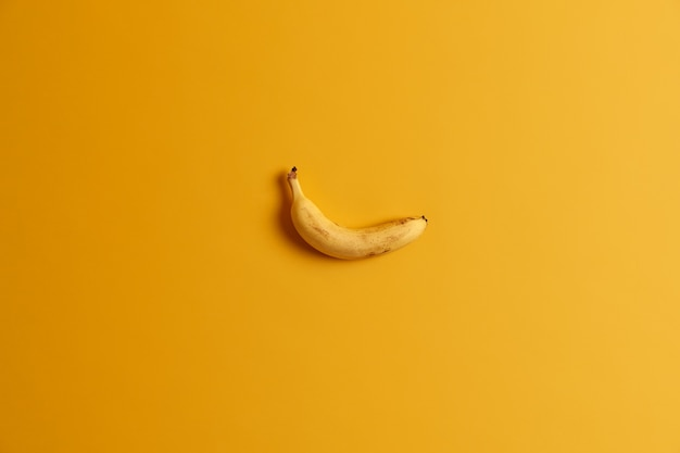 Single ripe delicious yellow banana isolated over studio background. bright color prevails. tropical fruit for your tasty snack. appetizing edible product. empty space for text or information