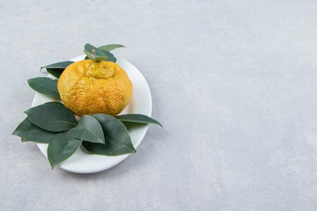 하얀 접시에 잎이 달린 잘 익은 귤 하나.