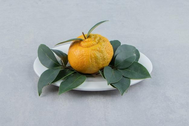 Один спелый мандарин с листьями на белой тарелке