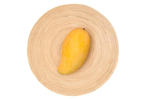 대나무 쟁반에 하나의 익은 태국 망고. 망고에 클리핑 패스가 있는 흰색 배경.