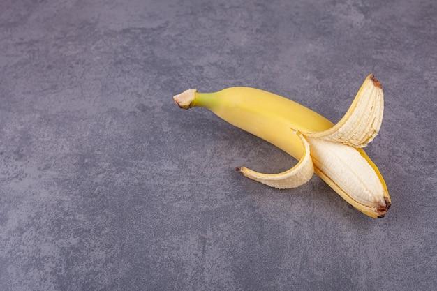 Один спелый желтый банан на камне.