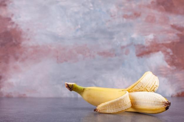 Single ripe yellow banana placed on stone background.