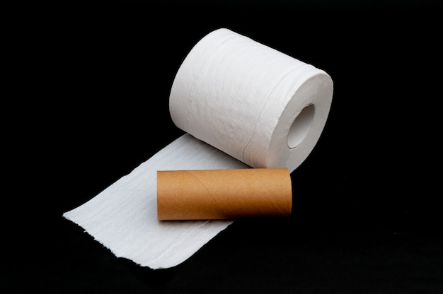 Single roll of unrolled white toilet paper and paper core tube isolated on black background