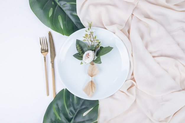Single rose on white plate with fake leaves and tablecloth.