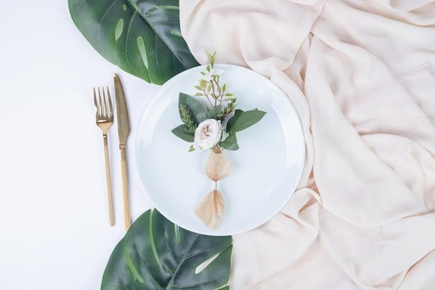 Rosa singola sul piatto bianco con foglie finte e tovaglia.