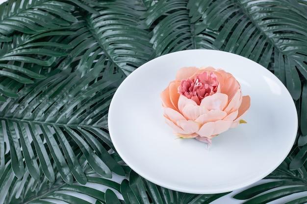 Singola rosa sulla zolla bianca con foglie finte.