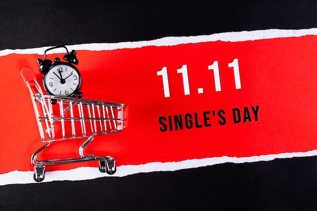 Single's day sale banner, 11.11. shopping cart on red paper with text.