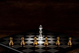 複数の金のチェスのポーンピースに囲まれたシングルシルバーキングチェス