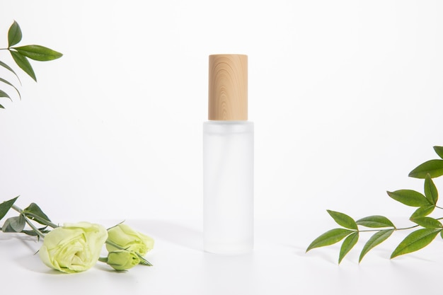 Single skincare bottle on a white background with a rose and green leaves