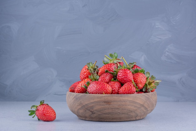 Single strawberry next to a wooden bowl of strawberries on marble background.