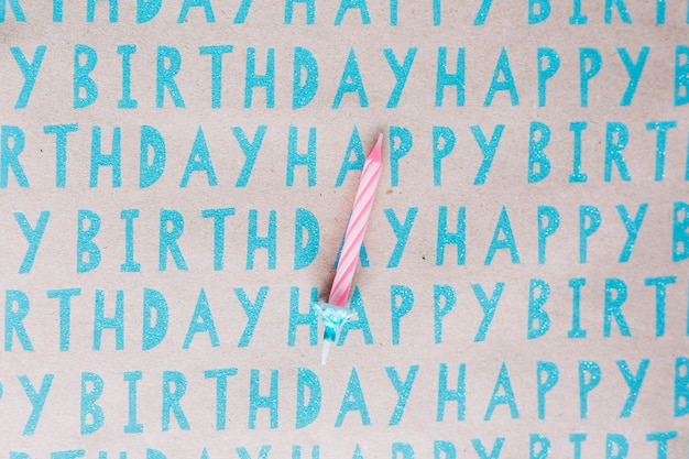 Single striped candle on happy birthday paper