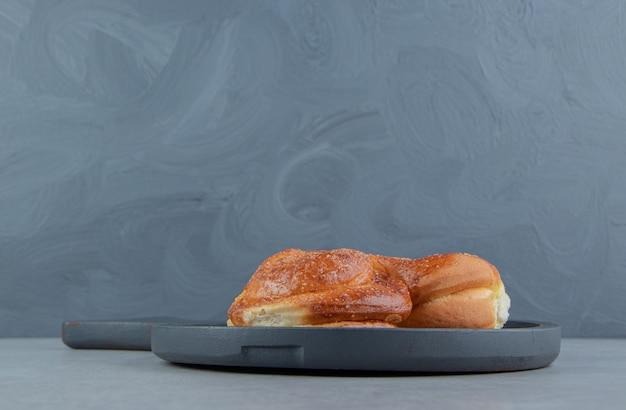 Single sweet pastry on black board.