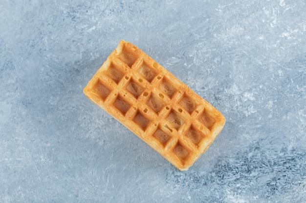 Single sweet waffle on marble background.