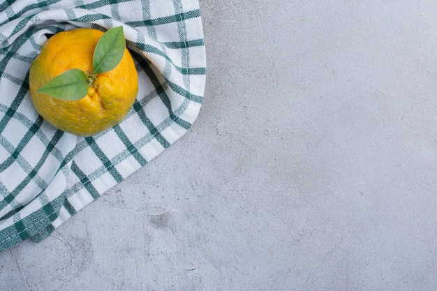 Одиночный мандарин на полотенце на мраморном фоне.