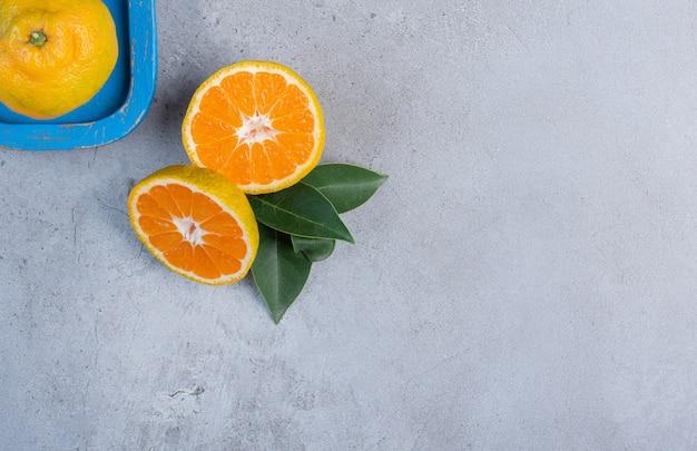Mandarino singolo su un piatto accanto a mandarini a fette con foglie su sfondo di marmo.