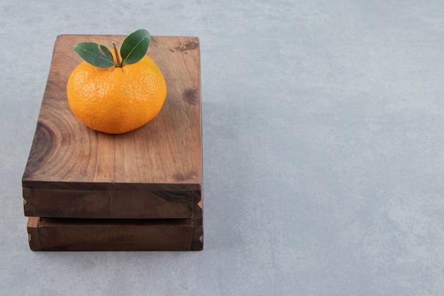 Один вкусный клементин на деревянной коробке