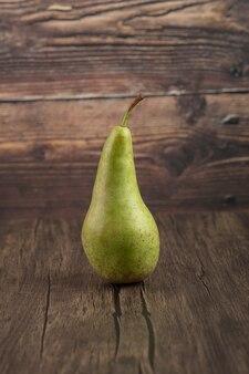 Singola pera fresca saporita disposta su superficie di legno