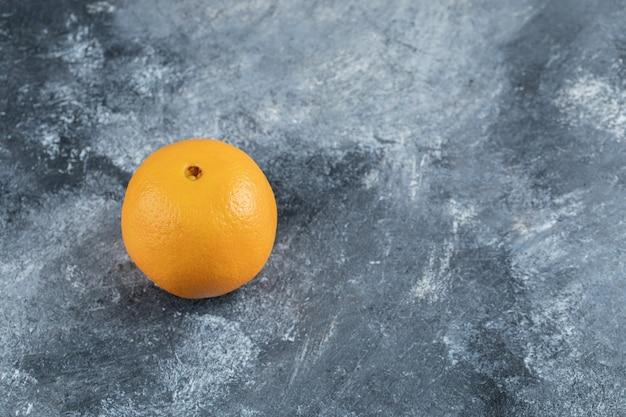 Singola arancia saporita sulla tavola di marmo.