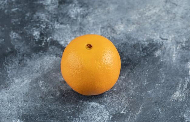Один вкусный апельсин на мраморном столе.