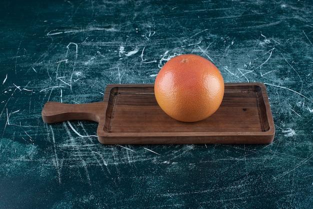 Одиночный вкусный апельсин на деревянной доске.