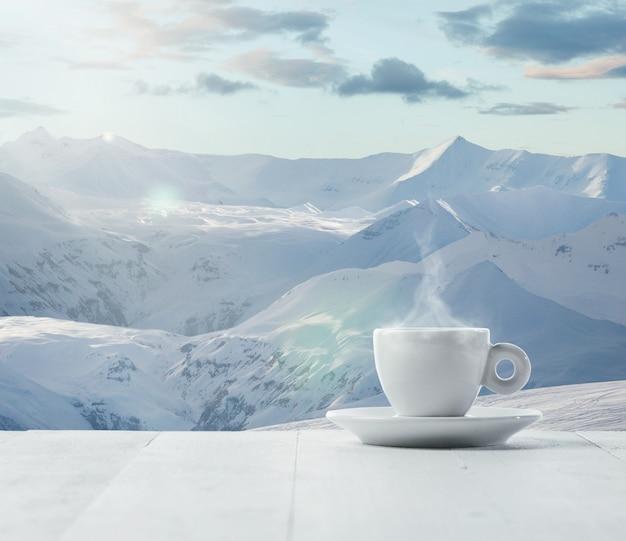 Одна чашка чая или кофе и пейзаж гор на фоне. чашка горячего напитка со снежным взглядом и облачным небом перед ним. тепло в зимний день, праздники, путешествия, новый год и рождество.